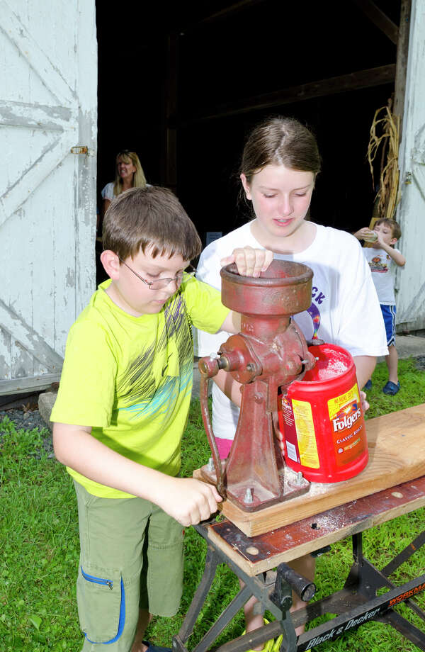 Matt Johnston, 9, and his sister Gabi Johnston, 11, of Easton, grind corn into cornmeal at Historic Bradley-Hubbell House in Easton during the 5th annual Citizens for Easton Farm Tour on Saturday, Aug. 10, 2013. Photo: Amy Mortensen / Connecticut Post Freelance