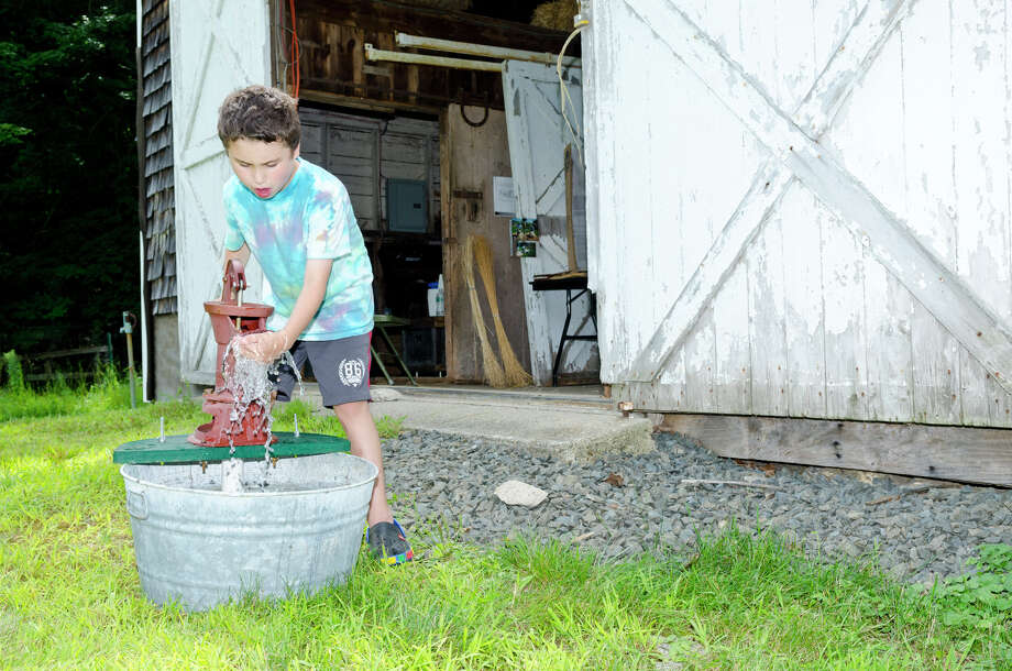 Nathaniel Miller, 9, of Westport, pumps water the old-fashioned way at Historic Bradley-Hubbell House in Easton during the 5th annual Citizens for Easton Farm Tour on Saturday, Aug. 10, 2013. Photo: Amy Mortensen / Connecticut Post Freelance