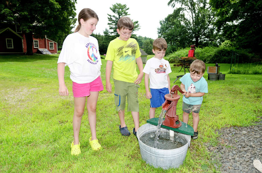 The Johnston family of Easton from left, Gabi, 11; Matt, 9; and Nate, 5 watch their brother Zach, 3, pump water at Historic Bradley-Hubbell House in Easton during the 5th annual Citizens for Easton Farm Tour on Saturday, Aug. 10, 2013. Photo: Amy Mortensen / Connecticut Post Freelance