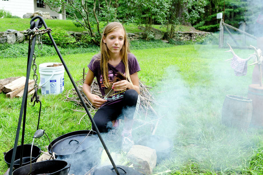 Madelyn Andrews, 13, of Easton, checks the fire during a Colonial cooking demonstration on the grounds of Historic Bradley-Hubbell House in Easton during the 5th annual Citizens for Easton Farm Tour on Saturday, Aug. 10, 2013. Photo: Amy Mortensen / Connecticut Post Freelance