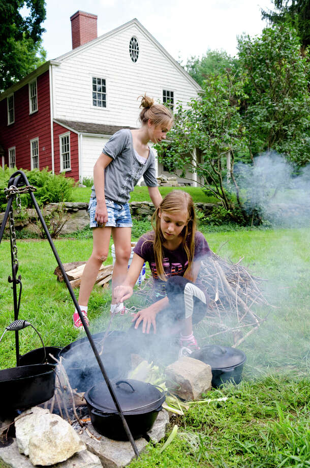 Madelyn Andrews, 13, of Easton, checks the fire during a Colonial cooking demonstration on the grounds of Historic Bradley-Hubbell House in Easton during the 5th annual Citizens for Easton Farm Tour on Saturday, Aug. 10, 2013. Andrews' sister, Shaeleigh Andrews, 10, grabs wood to add to the fire. Photo: Amy Mortensen / Connecticut Post Freelance