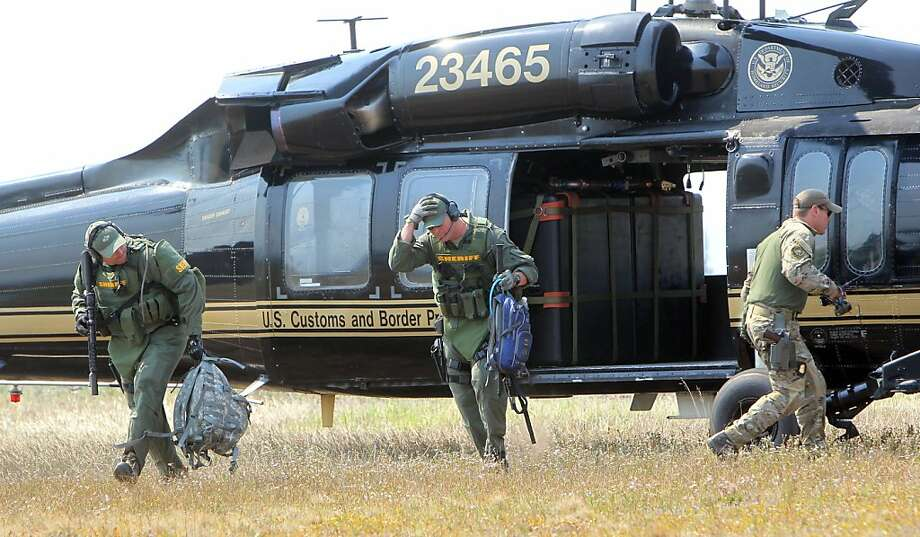 Law enforcement personnel scramble from a Black Hawk copter at Cascade Airport to join the search. Photo: Joe Jaszewski, Associated Press