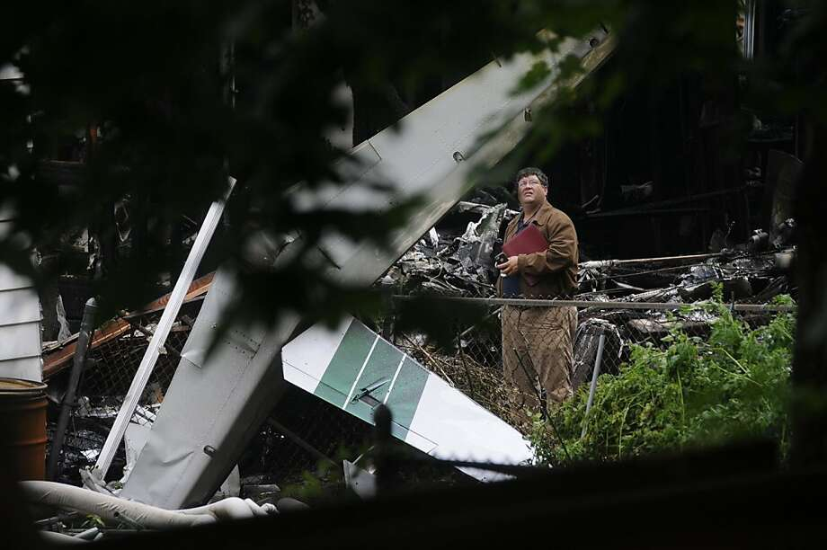An official surveys the scene of a plane crash in an East Haven, Conn., home. Two homes were hit and burst into flames in the fatal plane crash near Tweed New Haven Airport on Friday. Photo: Richard Messina, McClatchy-Tribune News Service