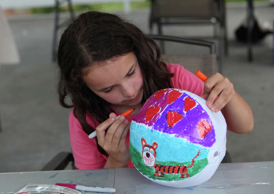 Ella Campfield, 10, of Fairfield, paints a ball during an Artist for a Day event at Sherman Green in Fairfield on Saturday, Aug. 10, 2013. World Artist Network sponsors the event which presents mini art labs for community members of all ages. Photo: BK Angeletti, B.K. Angeletti / Connecticut Post freelance B.K. Angeletti