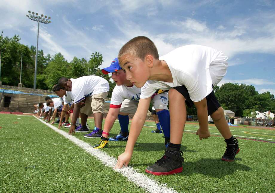 Joshua Hernandez, 11 participates in warm-up drills during Stamford Youth Foundation's Marcus Dixon McInerney Youth Football Camp at Stamford High School on Saturday, August 10, 2013. Photo: Lindsay Perry / Stamford Advocate