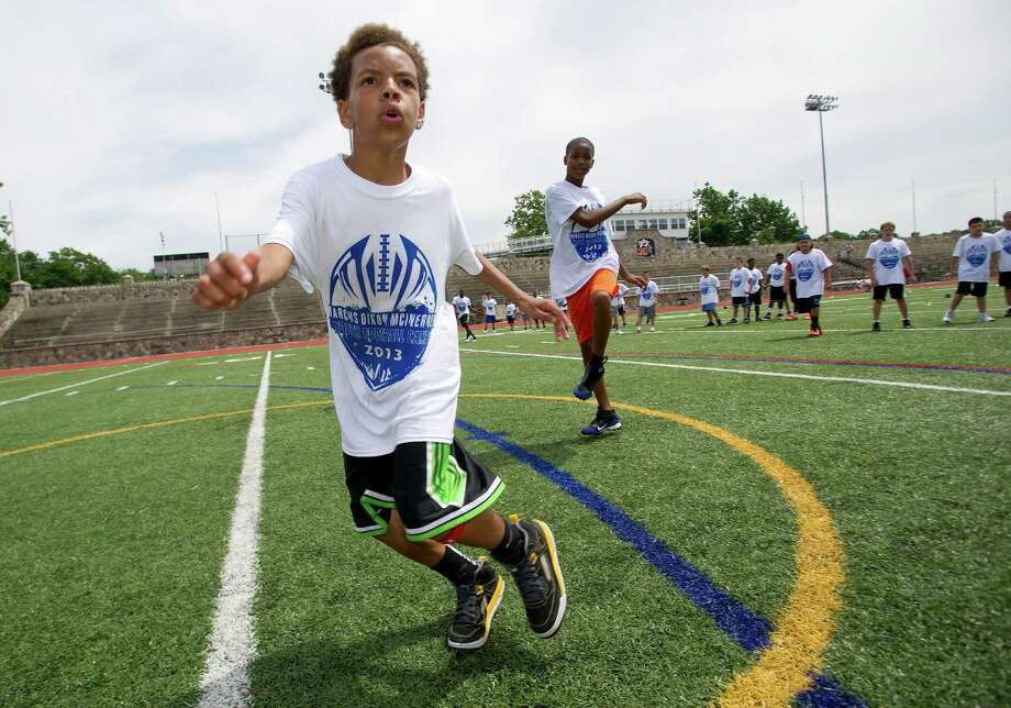 Lacaiye Compere, 12, participates in warm-up drills during Stamford Youth Foundation's Marcus Dixon McInerney Youth Football Camp at Stamford High School on Saturday, August 10, 2013. Photo: Lindsay Perry / Stamford Advocate