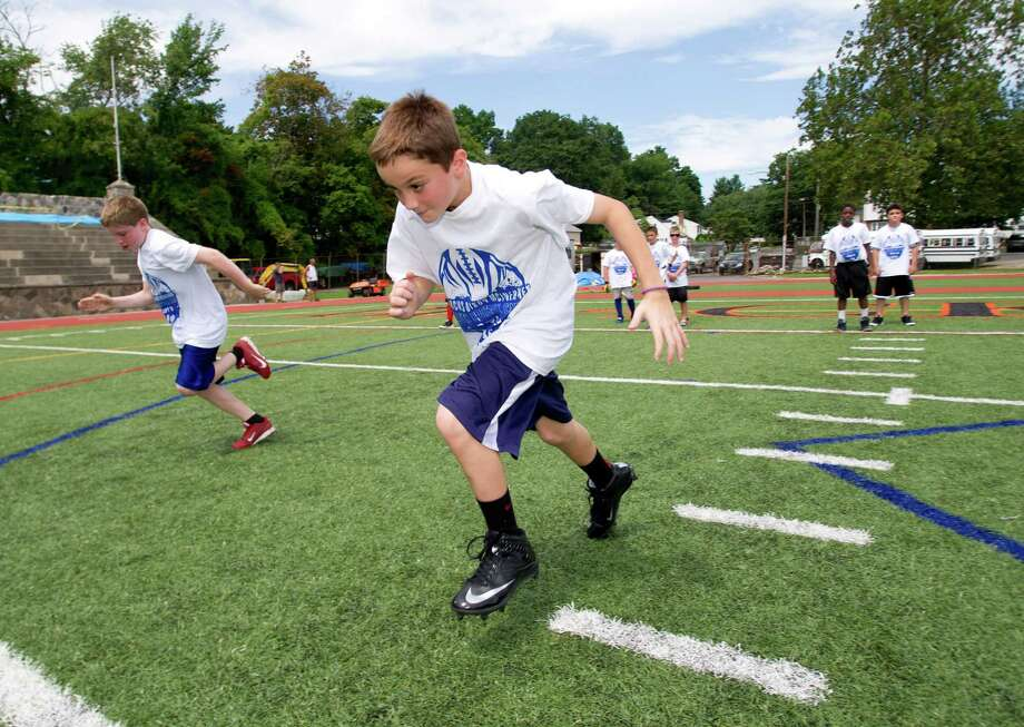 Robert Smeriglio, 11, participates in warm-up drills during Stamford Youth Foundation's Marcus Dixon McInerney Youth Football Camp at Stamford High School on Saturday, August 10, 2013. Photo: Lindsay Perry / Stamford Advocate