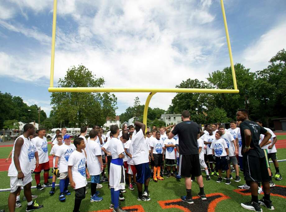 Players gather under the uprights before participating in warm-up drills during Stamford Youth Foundation's Marcus Dixon McInerney Youth Football Camp at Stamford High School on Saturday, August 10, 2013. Photo: Lindsay Perry / Stamford Advocate