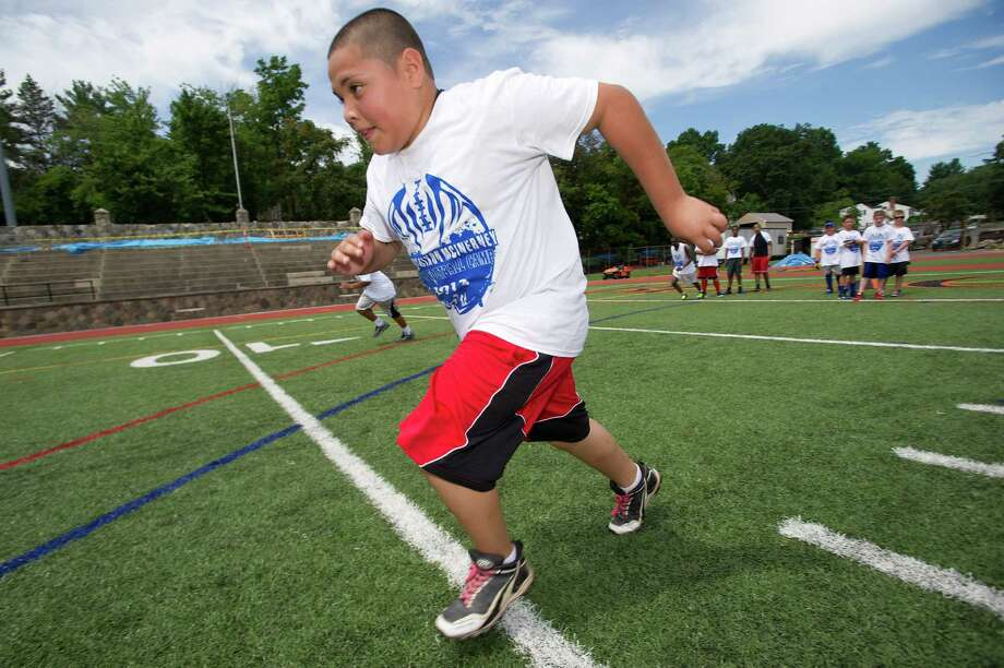 Jose Nieves, 12, participates in warm-up drills during Stamford Youth Foundation's Marcus Dixon McInerney Youth Football Camp at Stamford High School on Saturday, August 10, 2013. Photo: Lindsay Perry / Stamford Advocate