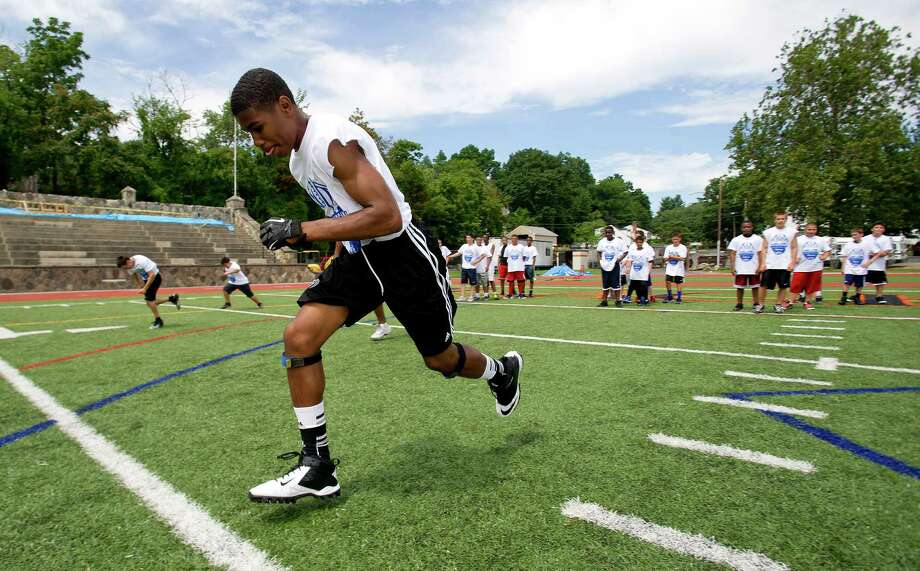 Teenagers participate in warm-up drills during Stamford Youth Foundation's Marcus Dixon McInerney Youth Football Camp at Stamford High School on Saturday, August 10, 2013. Photo: Lindsay Perry / Stamford Advocate