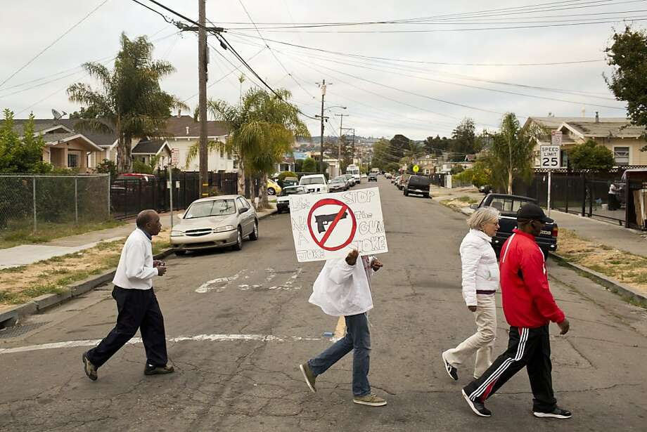 "Volunteers walk in East Oakland Friday night to talk with residents about combatting street violence. The sign reads: ""Life's not a joke; stop the gun smoke."" Photo: Jason Henry, Special To The Chronicle"