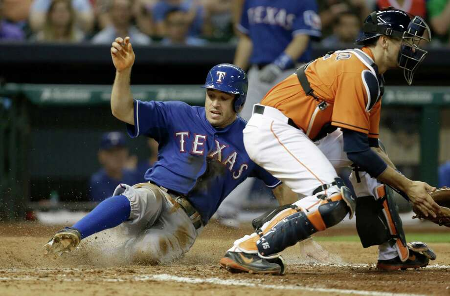 Texas Rangers' Ian Kinsler, left, slides across home plate to score as Houston Astros catcher Jason Castro waits for the ball in the eighth inning of a baseball game Friday, Aug. 9, 2013, in Houston. (AP Photo/Pat Sullivan) Photo: Pat Sullivan, Associated Press / AP