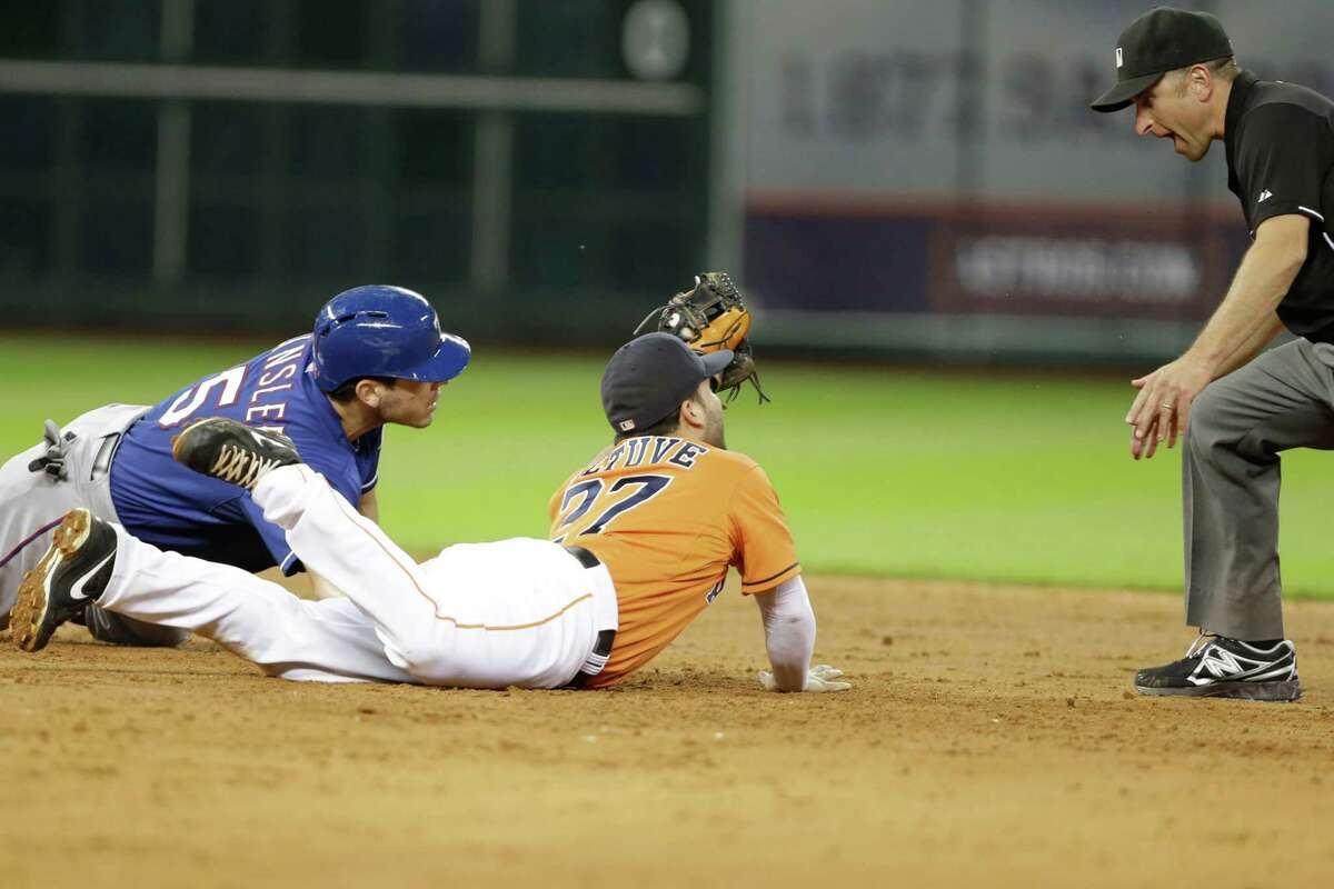 Texas Rangers' Ian Kinsler (5) and Houston Astros second baseman Jose Altuve (27) look at second base umpire Chris Guccione as he calls Kinsler safe in the sixth inning of a baseball game Friday, Aug. 9, 2013, in Houston. Kinsler was safe at second. (AP Photo/Pat Sullivan)