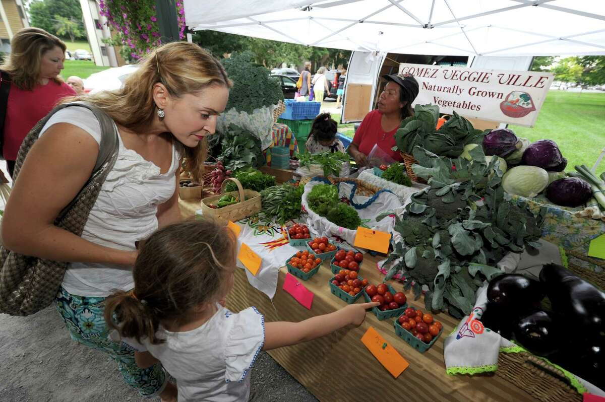 Sarah Nelson and her 5-year-old daughter Juliette look over the produce at the Gomez Veggie Ville booth during the Saratoga Summer Farmers' Market on Wednesday Aug. 7, 2013 in Saratoga Springs, N.Y. (Michael P. Farrell/Times Union)
