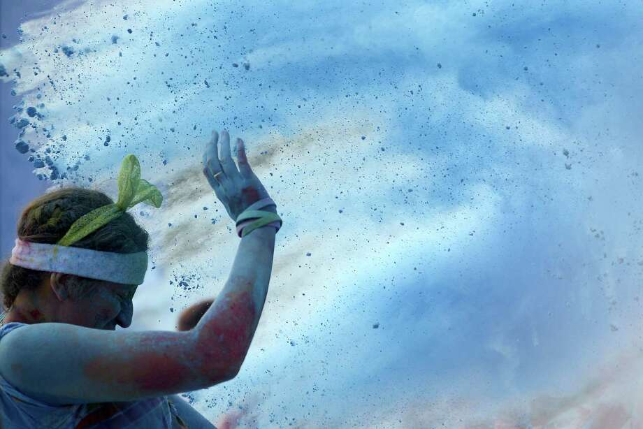 A participant of The Color Run Beijing reacts as they are showered with coloured powder in the blue zone during the event in Beijing on August 10, 2013.  Several thousand people took part in the 5 kilometre untimed race, during which participants were pelted with powder as they passed through four colour zones. Photo: WANG ZHAO, AFP/Getty Images / AFP ImageForum
