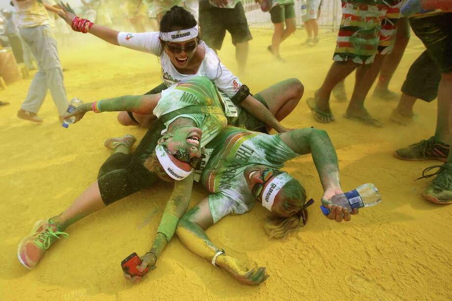 Competitors run through the yellow colour throw area during the Colour Run at the Beijing International Garden Expo park on August 10, 2013 in Beijing, China. It's the first time China hosts this event. Photo: Feng Li, Getty Images / 2013 Getty Images