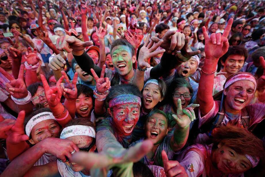 Competitors celebrate completing the Colour Run at the Beijing International Garden Expo park on August 10, 2013 in Beijing, China. It's the first time China hosts this event. Photo: Lintao Zhang, Getty Images / 2013 Getty Images
