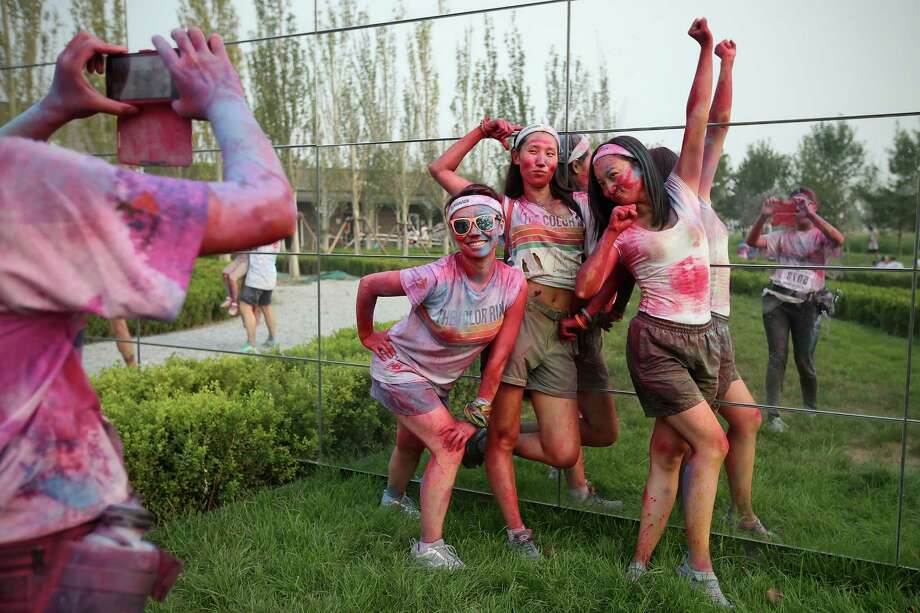 Competitors pose for photos after finish the Colour Run at the Beijing International Garden Expo park on August 10, 2013 in Beijing, China. It's the first time China hosts this event. Photo: Feng Li, Getty Images / 2013 Getty Images