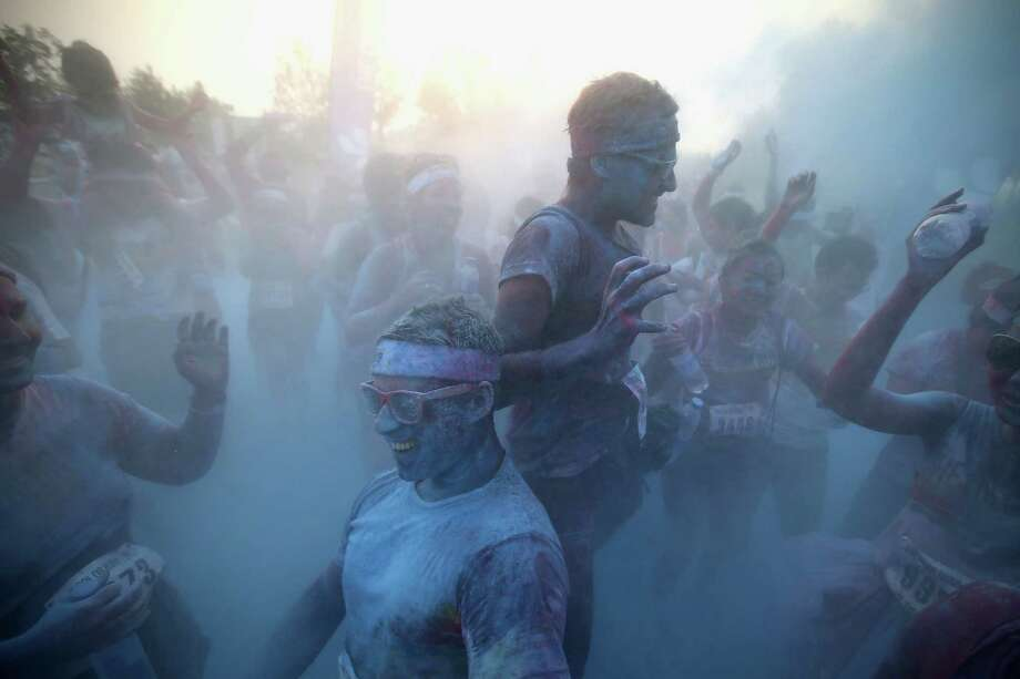 Competitors run through the blue colour throw area during the Colour Run at the Beijing International Garden Expo park on August 10, 2013 in Beijing, China. It's the first time China hosts this event. Photo: Feng Li, Getty Images / 2013 Getty Images