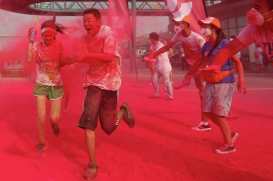 Competitors run through the red colour throw area during the Colour Run at the Beijing International Garden Expo park on August 10, 2013 in Beijing, China. It's the first time China hosts this event. Photo: Feng Li, Getty Images / 2013 Getty Images