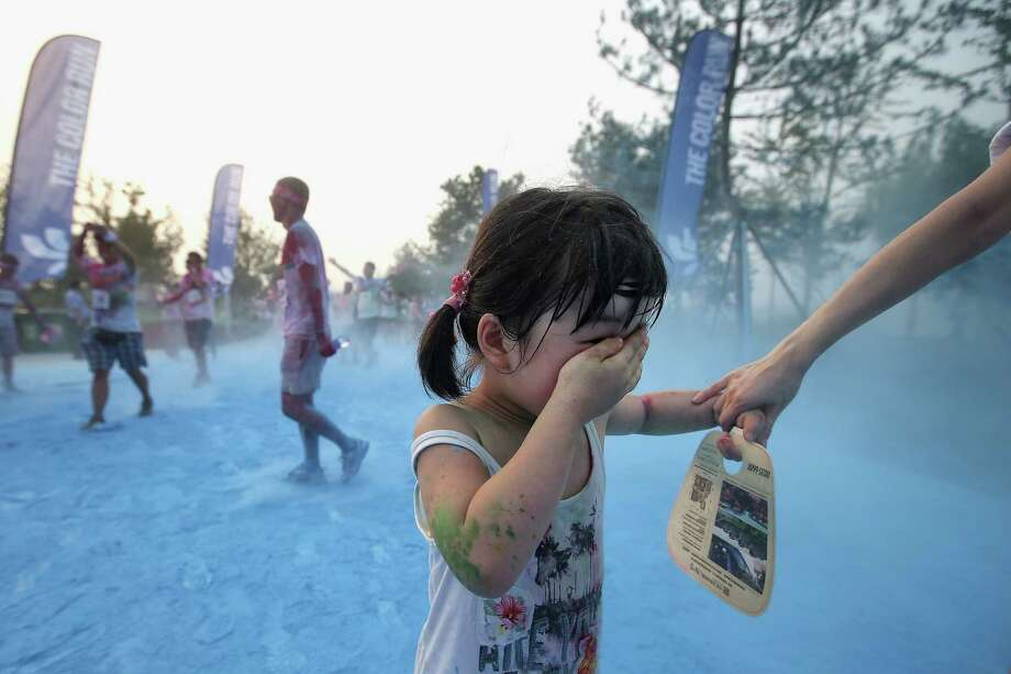 A liitle competitor runs through the blue colour throw area during the Colour Run at the Beijing International Garden Expo park on August 10, 2013 in Beijing, China. It's the first time China hosts this event. Photo: Feng Li, Getty Images / 2013 Getty Images