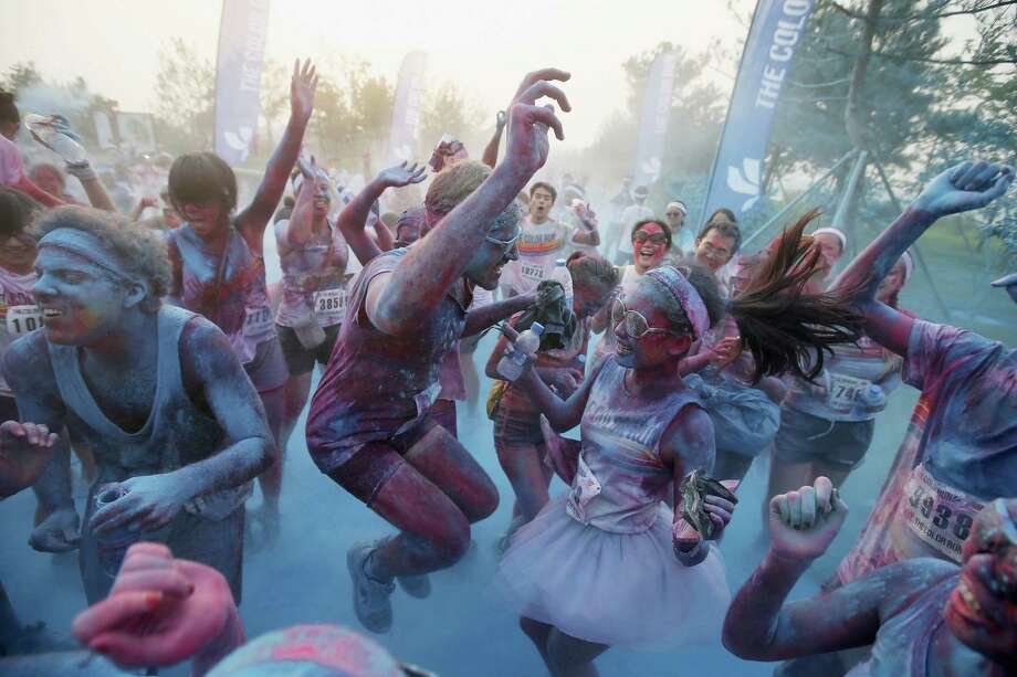 Competitors dance as running through the blue colour throw area during the Colour Run at the Beijing International Garden Expo park on August 10, 2013 in Beijing, China. It's the first time China hosts this event. Photo: Feng Li, Getty Images / 2013 Getty Images