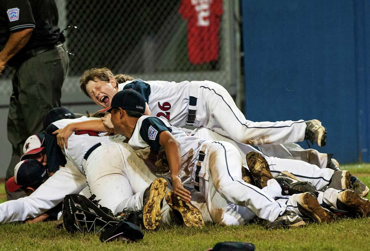 #26 Drew Rogers jumps on top of the pile as the Westport, CT team celebrates winning the Little League 12-year-old New England championship game against Lincoln, RI played at Breen Field, Bristol, CT on Saturday, August 10th, 2013.