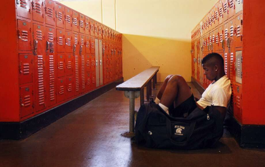 Marcus Brown sits in the locker room before football practice starts at Mcclymonds high school on Monday, August 05, 2013 in Oakland, Calif. Photo: Rohan Smith, The Chronicle