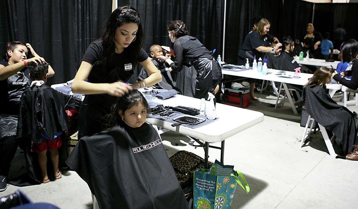 Jeylee Oviedo, 4, gets her hair cut by Marisol Morales of the Paul Mitchell the school San Antonio Aug. 10, 2013 during the San Antonio Back 2 School Expo at the Freeman Coliseum Expo Hall. Over 50 vendors participated in the event that offered a variety of items for back to school, including toothbrushes, back packs, crayon, haircut and shots. Jeylee and her mom waited about an hour to get her haircut for free. Paul Mitchell the school San Antonio had about eight students cutting hair at the expo which lasted from 9 a.m until 3 p.m.