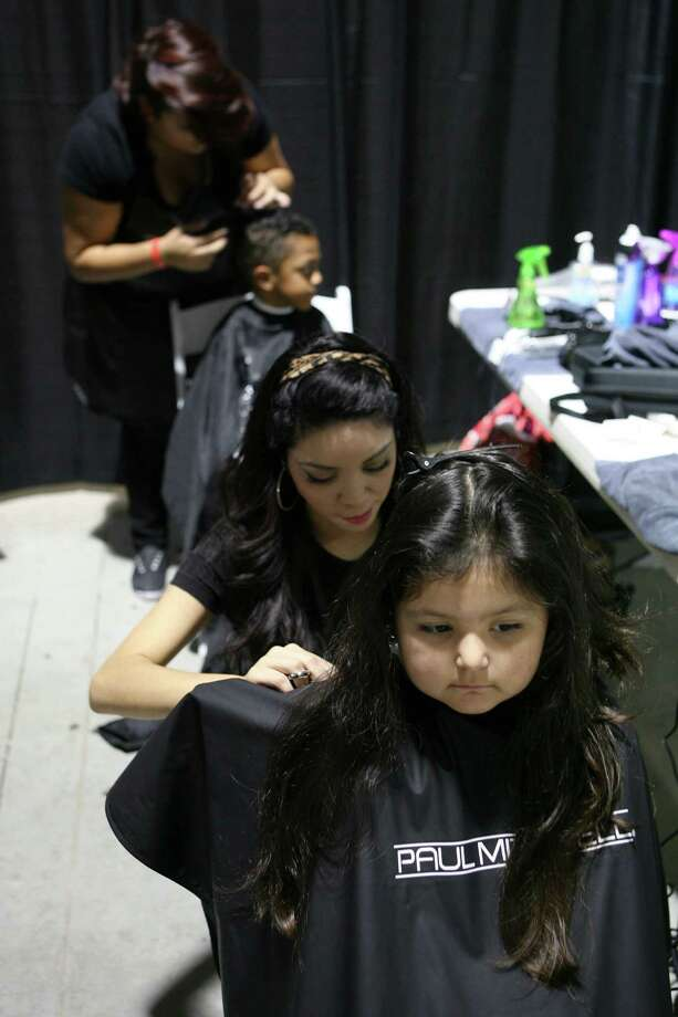 Jeylee Oviedo, 4, gets her hair cut by Marisol Morales of the Paul Mitchell the school San Antonio Aug. 10, 2013 during the San Antonio Back 2 School Expo at the Freeman Coliseum Expo Hall. Over 50 vendors participated in the event that offered a variety of  items for back to school, including toothbrushes, back packs, crayon, haircut and shots.  Jeylee and her mom waited about an hour to get her haircut for free. Paul Mitchell the school San Antonio had about eight students cutting hair at the expo which lasted from 9 a.m until 3 p.m. Photo: Cynthia Esparza, For San Antonio Express-News / For San Antonio Express-News