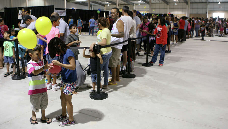 Domynyk Mendez (left), 5, and Aniyah Mendez, 7, play with a woopee cushion they got from the Dave & Buster's booth as they wait in line for free haircuts during the San Antonio Back 2 School Expo Aug. 10, 2013 at the Freeman Coliseum Expo Hall. Over 50 vendors participated in the event that offered a variety of  items for back to school, including toothbrushes, back packs, crayon, haircut and shots. Photo: Cynthia Esparza, For San Antonio Express-News / For San Antonio Express-News