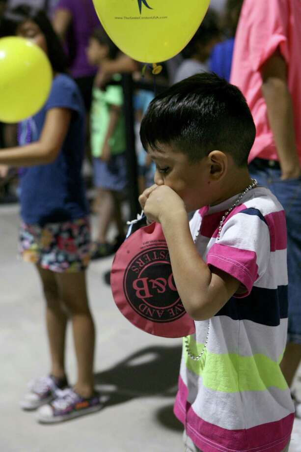 Domynyk Mendez (left), 5 plays with a woopee cushion he got from the Dave & Buster's booth Aug. 10, 2013 while he and his family wait in line for free haircuts during the San Antonio Back 2 School Expo at the Freeman Coliseum Expo Hall. Over 50 vendors participated in the event that offered a variety of  items for back to school, including toothbrushes, back packs, crayon, haircuts and shots. Photo: Cynthia Esparza, For San Antonio Express-News / For San Antonio Express-News