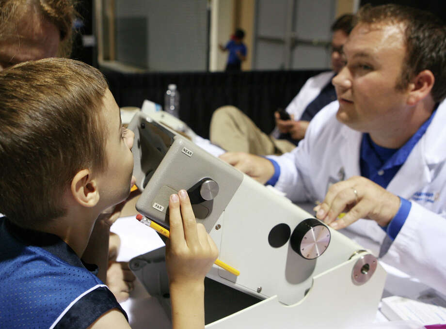 Freddie Weisenmiller, 5, gets his eyes checked by Luke Phillips, a vision center manager at Walmart during the San Antonio Back 2 School Expo Aug. 10, 2013 at the Freeman Coliseum Expo Hall. Seven vision center managers from Walmart were at the expo to provide the eye checks for children. Over 50 vendors participated in the event that offered a variety of  items for back to school, including toothbrushes, back packs, crayon, haircuts and shots. Photo: Cynthia Esparza, For San Antonio Express-News / For San Antonio Express-News