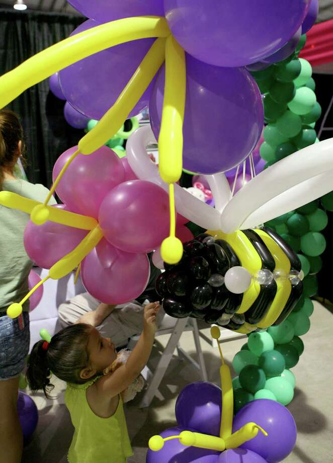 Nisa Payan, 2, touches a bee balloon pinata at the Almapaints booth Aug. 10, 2013 during the San Antonio Back 2 School Expo at the Freeman Coliseum Expo Hall. Over 50 vendors participated in the event that offered a variety of  items for back to school, including toothbrushes, back packs, crayon, haircuts and shots. Photo: Cynthia Esparza, For San Antonio Express-News / For San Antonio Express-News