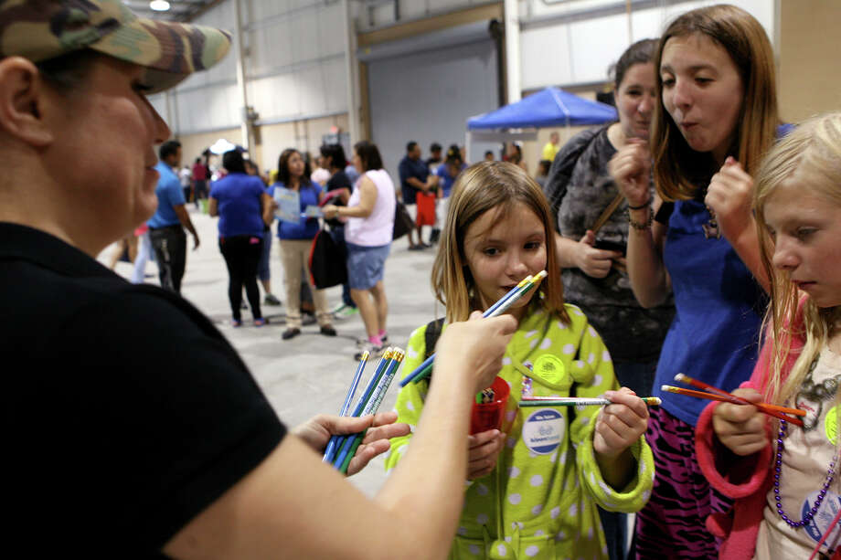Stacey Crawford hands out O'Reilly Auto Parts pencils Aug. 10, 2013 to Kiaran (left), Aria and Neko McKay during the San Antonio Back 2 School Expo at the Freeman Coliseum Expo Hall. Over 50 vendors participated in the event that offered a variety of  items for back to school, including toothbrushes, back packs, crayon, haircuts and shots. Photo: Cynthia Esparza, For San Antonio Express-News / For San Antonio Express-News