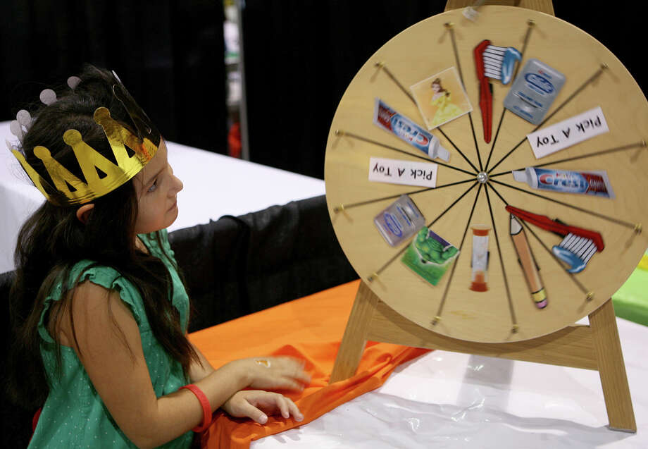 Daisy Jemel, 7 waits for the wheel to stop at the Cute Smiles 4 Kids booth during the San Antonio Back 2 School Expo Aug. 10, 2013 at the Freeman Coliseum Expo Hall. Over 50 vendors participated in the event that offered a variety of  items for back to school, including toothbrushes, back packs, crayon, haircut and shots. Photo: Cynthia Esparza, For San Antonio Express-News / For San Antonio Express-News
