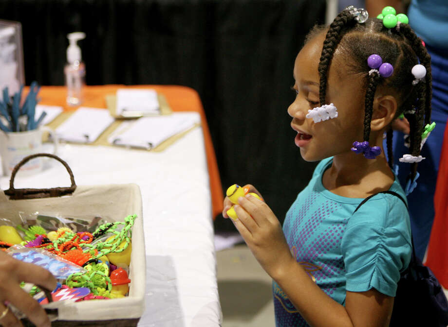 Jamaria Borisce picks a prize at the Cute Smiles 4 Kids booth during the San Antonio Back 2 School Expo Aug. 10, 2013 at the Freeman Coliseum Expo Hall. Over 50 vendors participated in the event that offered a variety of  items for back to school, including toothbrushes, back packs, crayons, haircuts and shots. Photo: Cynthia Esparza, For San Antonio Express-News / For San Antonio Express-News