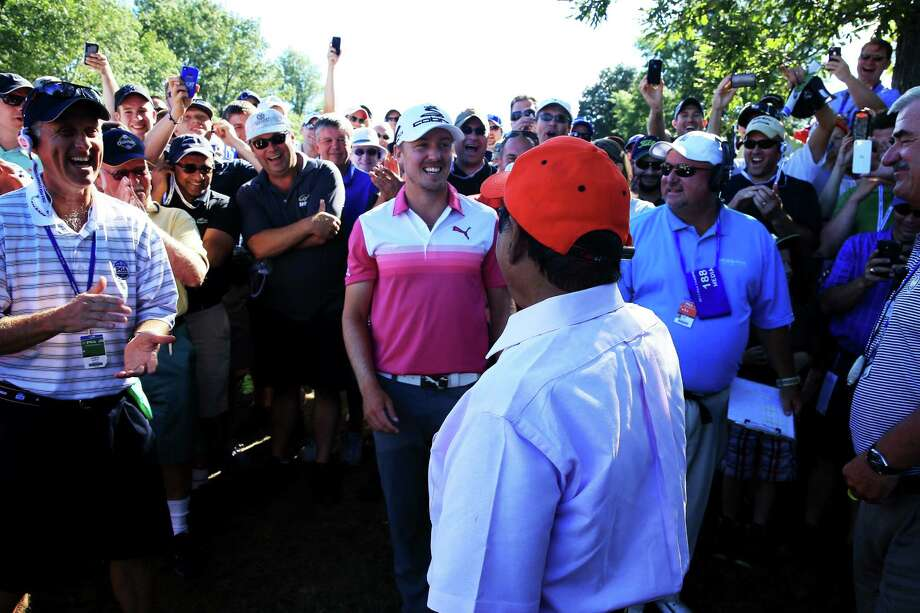 Jonas Blixt (front left) talks with Muhammad Khokhar after the Swede's tee shot landed in the gallery member's pocket on the 18th hole. Photo: David Cannon / Getty Images