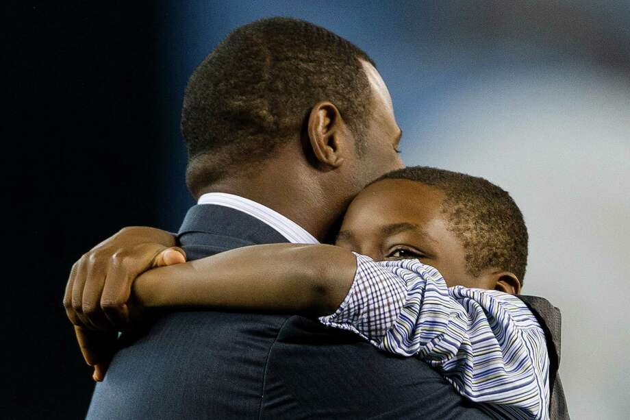 Tevin Griffey, right, hangs from his father, Ken Griffey Jr., left, during Junior's induction ceremony. Photo: JORDAN STEAD, SEATTLEPI.COM / SEATTLEPI.COM