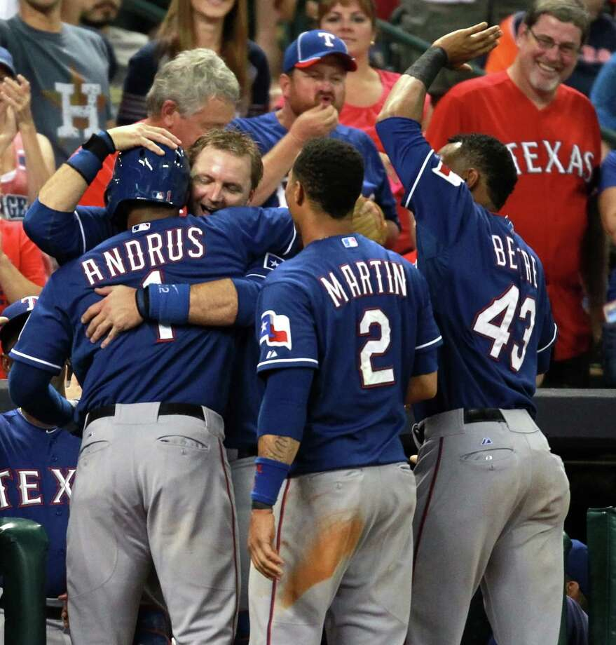 Elvis Andrus #1 of the Texas Rangers is hugged by teammate A.J. Pierzynski #12 during the seventh inning against the Houston Astros on August 10, 2013 at Minute Maid Park in Houston. Photo: Eric Christian Smith, Getty Images / 2013 Getty Images