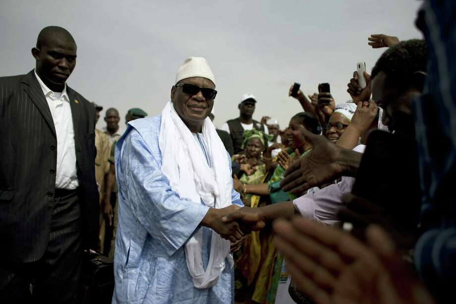 Malian presidential candidate Ibrahim Boubacar Keita, known by his initials IBK, shakes hands with supporters as he arrives at the airport in Sevare.