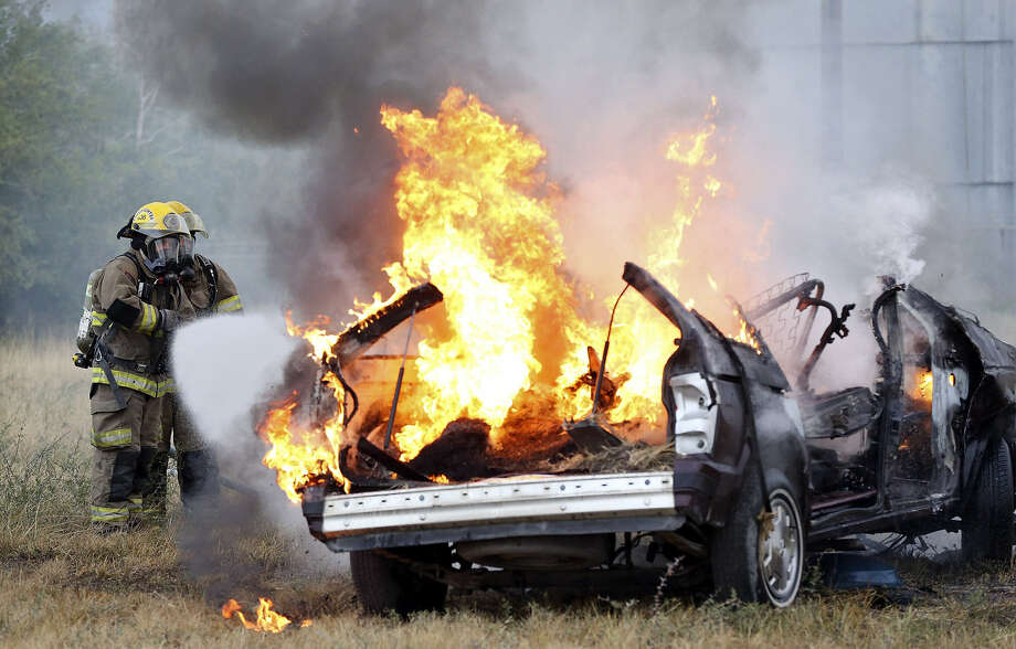 Karnes City volunteer firefighters work on a vehicle fire during training. The county's EMS has struggled to keep up with the surge of accidents and injuries since the boom. Photo: Edward A. Ornelas / San Antonio Express-News