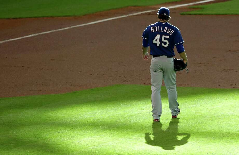 Texas Rangers starting pitcher Derek Holland steps off the mound in the first inning of a baseball game against the Houston Astros Saturday, Aug. 10, 2013, in Houston. (AP Photo/Pat Sullivan) Photo: Pat Sullivan, Associated Press / AP