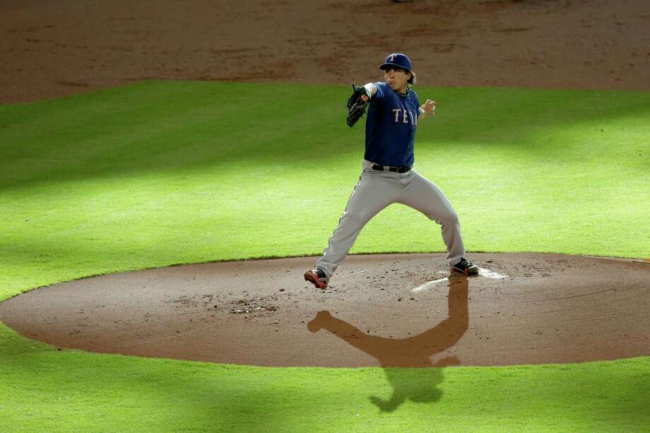 Texas Rangers' Derek Holland delivers a pitch against the Houston Astros in the first inning of a baseball game Saturday, Aug. 10, 2013, in Houston. (AP Photo/Pat Sullivan) Photo: Pat Sullivan, Associated Press / AP