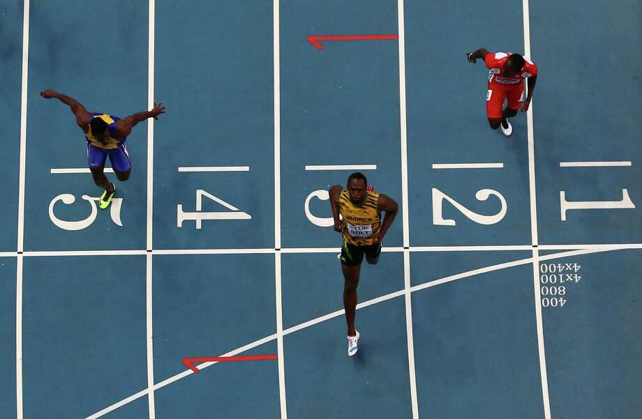 World-record holder Usain Bolt (center) crosses the finish line ahead of Ramon Gittens (left) and Rondel Sorrillo in an opening heat of the 100 meters. Photo: Paul Gilham / Getty Images