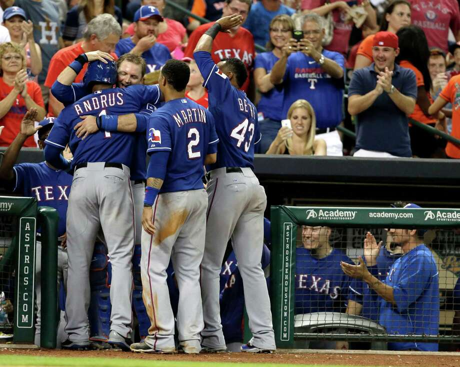 Texas Rangers' Elvis Andrus (1) is hugged by teammate A.J. Pierzynski after hitting his first home run in the seventh inning of a baseball game against the Houston Astros, Saturday, Aug. 10, 2013, in Houston. Rangers' Jurickson Profar also scored on the hit. (AP Photo/Pat Sullivan) Photo: Pat Sullivan, Associated Press / AP