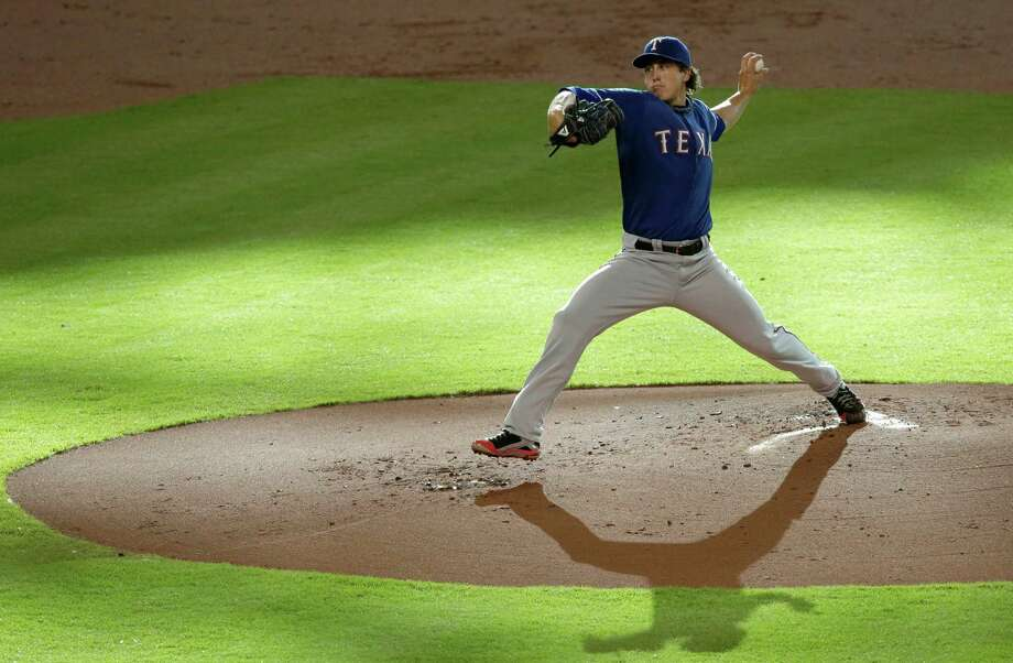 Texas Rangers' Derek Holland delivers a pitch against the Houston Astros in the first inning of a baseball game, Saturday, Aug. 10, 2013, in Houston. (AP Photo/Pat Sullivan) Photo: Pat Sullivan, Associated Press / AP