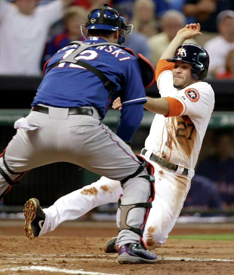 Houston Astros' Jose Altuve (27) is tagged out by Texas Rangers catcher A.J. Pierzynski (12) as he tries to score from second base on a Jason Castro single in the third inning of a baseball, Saturday, Aug. 10, 2013, in Houston. (AP Photo/Pat Sullivan) Photo: Pat Sullivan, Associated Press / AP