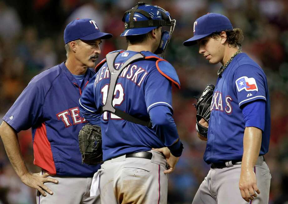 Texas Rangers starting pitcher Derek Holland, right, gets a visit to the mound from pitching coach Mike Maddux, left, and catcher A.J. Pierzynski (12) after loading the bases against the Houston Astros in the sixth inning of a baseball game, Saturday, Aug. 10, 2013, in Houston. (AP Photo/Pat Sullivan) Photo: Pat Sullivan, Associated Press / AP