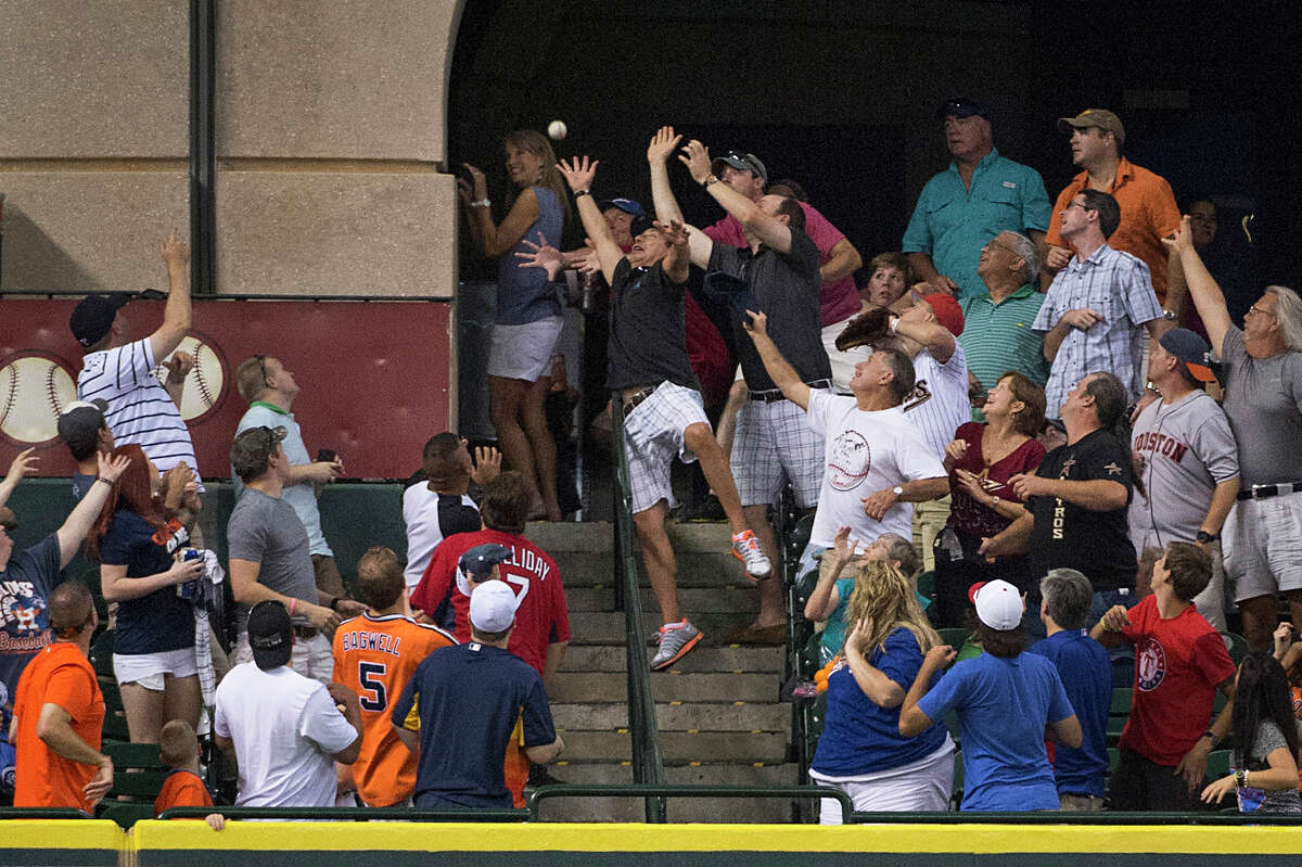 Fans in the Crawford Boxes reaches for a home run off the bat of Texas Rangers' Elvis Andrus during the seventh inning of a baseball game against the Houston Astros at Minute Maid Park on Saturday, Aug. 10, 2013, in Houston.